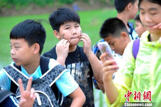 一名学生体验插秧后脸上沾了泥。 蒋雪林 摄