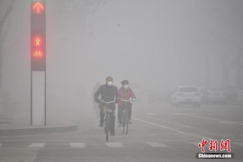 2016年2月12日,山东多地遭遇雾霾天气。市民在大雾笼罩下的山东省聊城市街头骑行。 图片来源:视觉中国