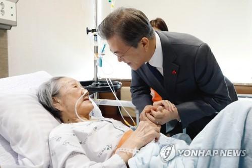 1月4日上午,在首尔延世大学医疗院,文在寅探望受害慰安妇金福童,祝这位年过九旬仍为女权奔走呼号的老人早日康复。图片来源:韩联社。