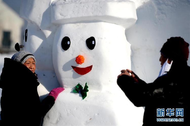 1月11日,游客在哈尔滨外滩赏冰乐雪园的奇趣雪人谷园区内观赏形态各异的雪人雕塑并合影留念。当日,2018座雪人雕塑在哈尔滨外滩赏冰乐雪园的奇趣雪人谷园区内展出,吸引来自各地的游客前来观赏。3.jpg