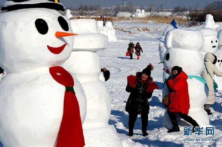 1月11日,游客在哈尔滨外滩赏冰乐雪园的奇趣雪人谷园区内观赏形态各异的雪人雕塑并合影留念。当日,2018座雪人雕塑在哈尔滨外滩赏冰乐雪园的奇趣雪人谷园区内展出,吸引来自各地的游客前来观赏。4.jpg