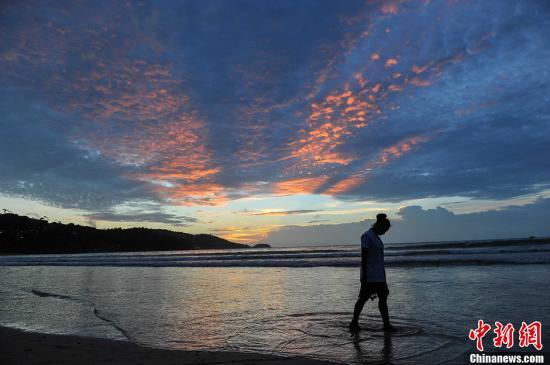 泰国普吉岛,图为一名游客从海滩上走过。洪坚鹏 摄