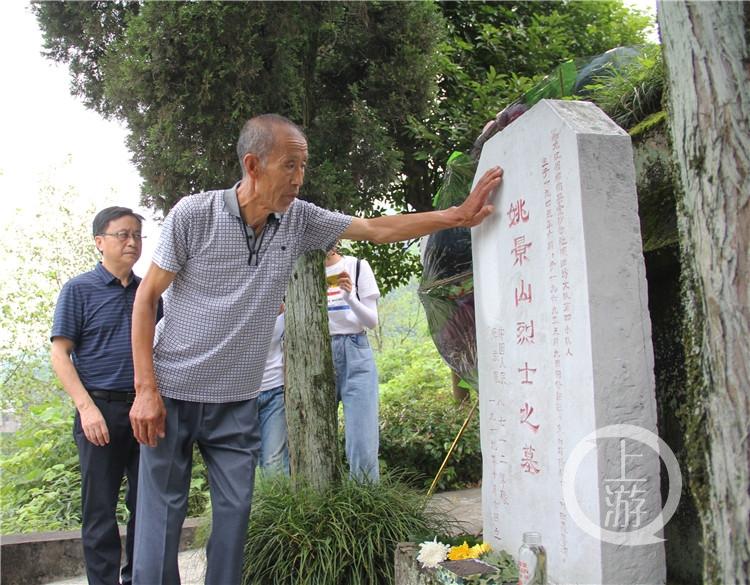 71岁的姚景海抚摸着大哥姚景山烈士的墓碑。_副本.jpg