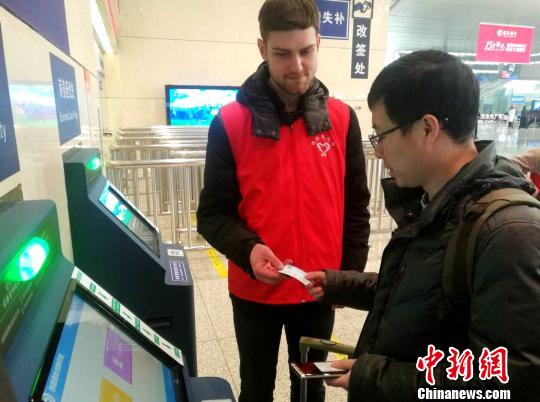 一名白俄罗斯留学生帮助乘客取高铁票。 刘鹏 摄