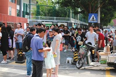 """2017年6月17日,北京,又到了每年一度的""""幼升小""""报名时间,家长一早便领着孩子,顶着高温到学校门口排队。图/视觉中国"""