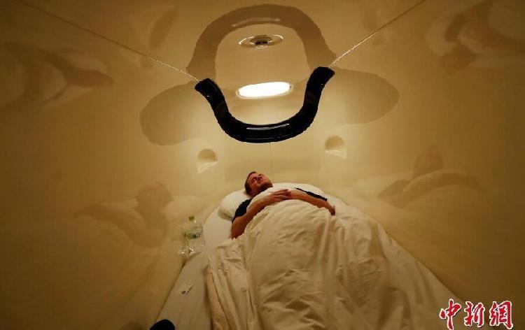 """日本东京的胶囊酒店里,一名来自美国的客人躺在他的床上。睡觉不老实的朋友,就不用考虑这样的""""局促""""体验了。.jpg"""