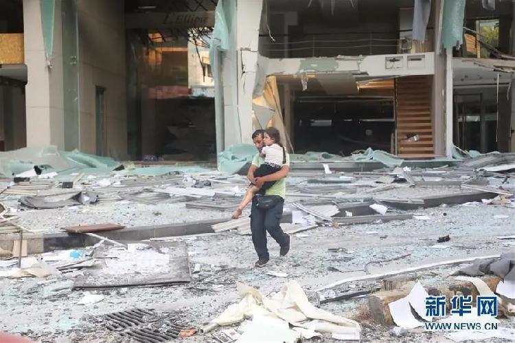 ▲8月4日,在黎巴嫩首都贝鲁特,一名男子抱着孩子走过严重受损的建筑。新华社发(比拉尔·贾维希 摄)